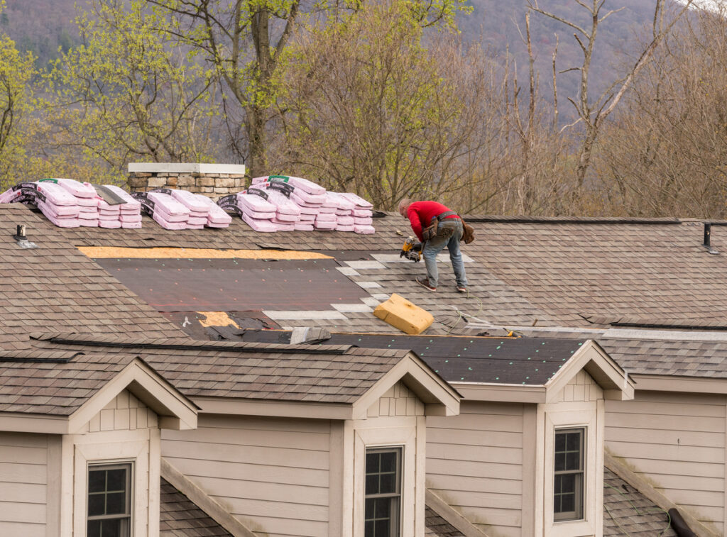 A roofing contractor replacing a roof on a house.