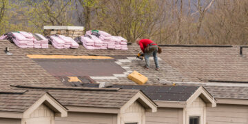 Roofing contractor removing the old shingles from a roof ready for reroofing